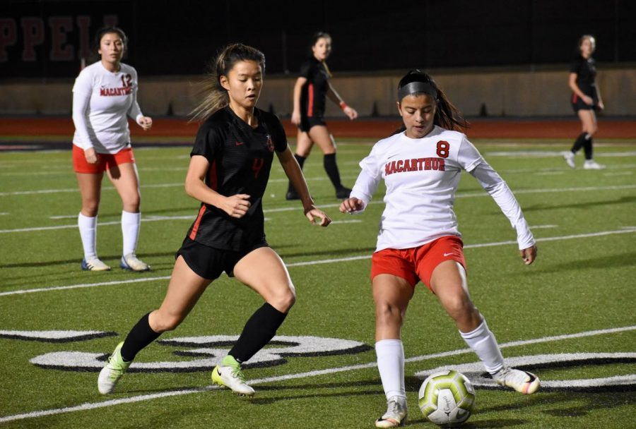 Coppell+sophomore+forward+Michelle+Pak+defends+against+Irving+MacArthur+Friday+night+at+Buddy+Echols+Field.+The+Cowgirls+defeated+the+Cardinals%2C+5-1.