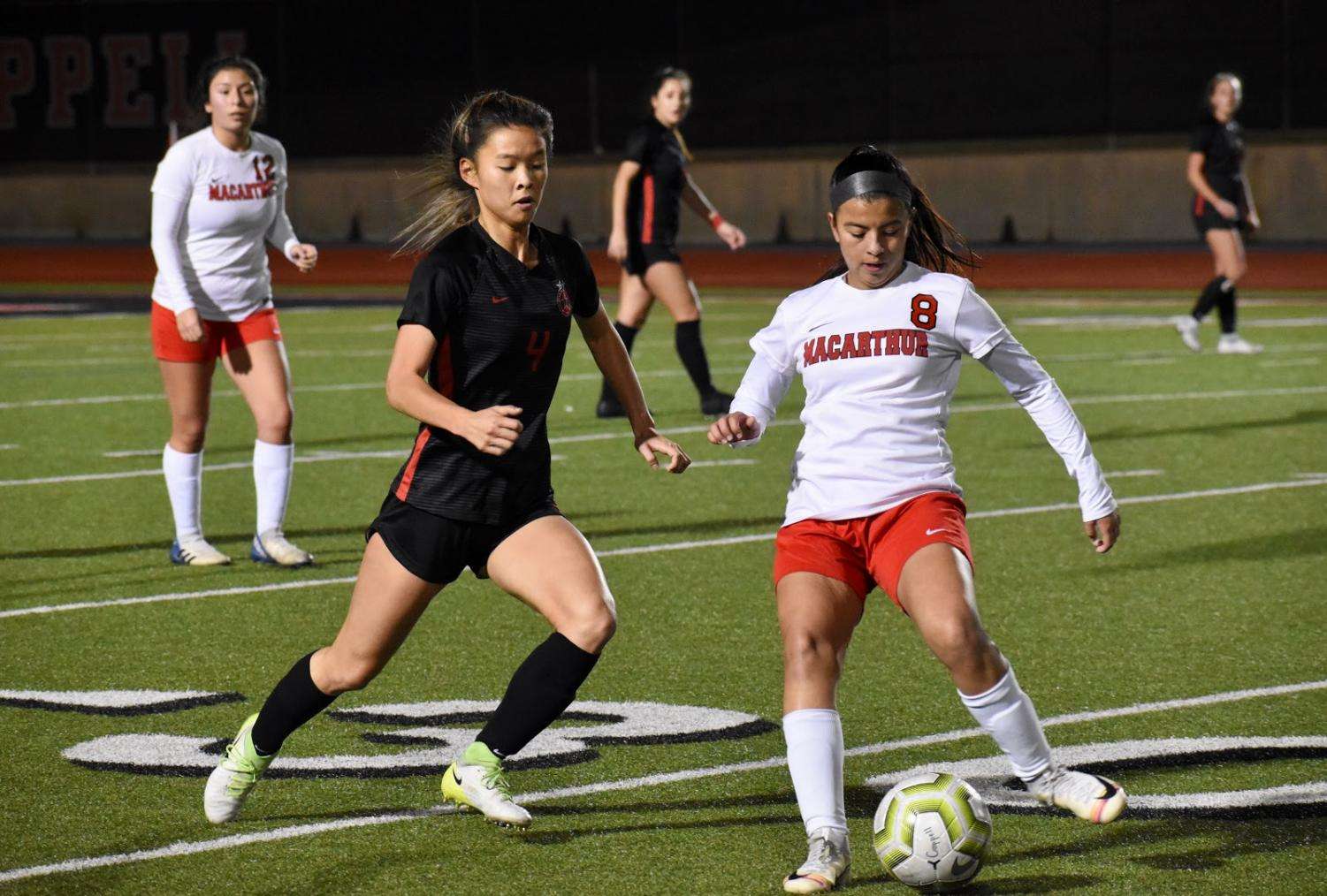 Coppell sophomore forward Michelle Pak defends against Irving MacArthur Friday night at Buddy Echols Field. The Cowgirls defeated the Cardinals, 5-1.