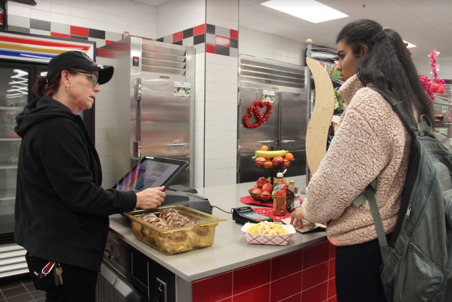 Coppell High school lunch lady Tarja Kuvaja checks out senior Lalitha Turaga during A lunch on Monday. The Child Nutrition Department sets prices for the products in the C-store to reimburse the department. Photo by Neveah Jones.