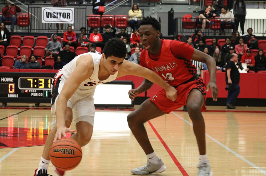 Coppell senior forward Adam Moussa protects the ball from Irving McArthur junior Davion Daily on Jan 21 in the CHS Arena. The Cowboys face Flower Mound Marcus tomorrow at 8 p.m. in the CHS Arena.