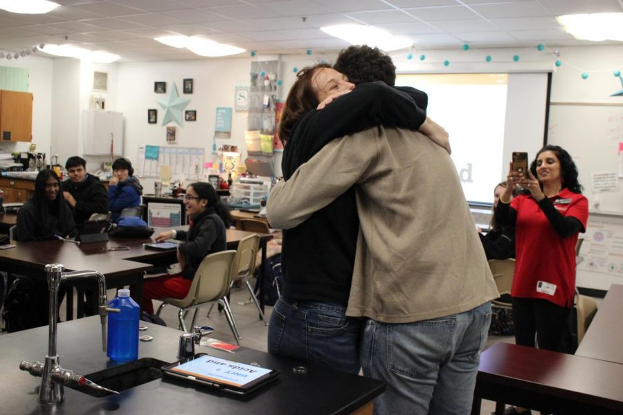 Coppell High School chemistry teacher Amy Snyder embraces CHS senior Cole Krautkramer after being given her banquet invitation on Thursday during fifth period. Every year, each student in the top five percent chooses a teacher to honor at the Coppell Education Foundation Recognition Banquet, which is April 20 at the Embassy Suites DFW North in Grapevine.
