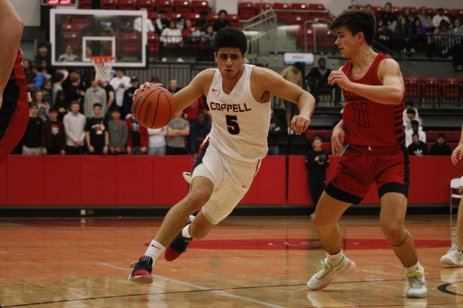 Coppell senior guard Adam Moussa dribbles around Marcus junior guard Nick Donnelly on Friday in the CHS Arena. The Cowboys held the lead throughout the entirety of a close game and defeated the Marauders 65-61.