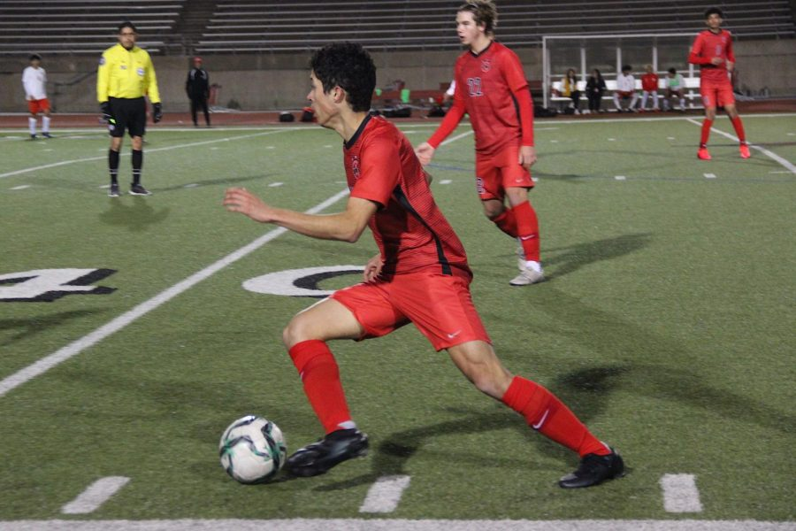 Coppell+senior+midfielder+Caleb+Razo+passes+at+Buddy+Echols+Field+on+Friday+against+MacArthur.+Cowboys+defeated+the+Cardinals%2C+2-1.+