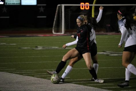 Coppell junior defender Emma Hubert fights for possession against Hebron at Buddy Echols Field on Tuesday. The Cowgirls defeated the Hawks, 4-3.