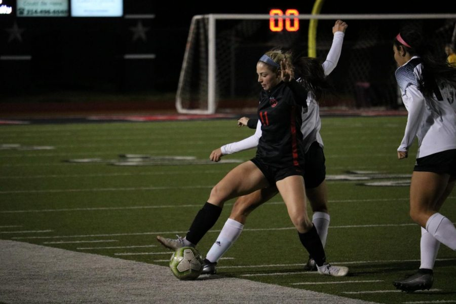 Coppell+junior+defender+Emma+Hubert+fights+for+possession+against+Hebron+at+Buddy+Echols+Field+on+Tuesday.+The+Cowgirls+defeated+the+Hawks%2C+4-3.