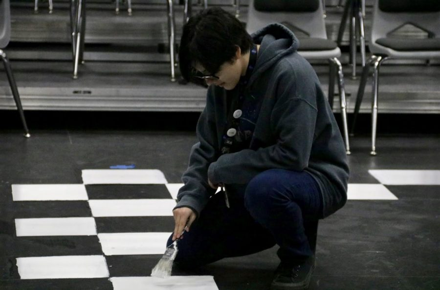 "Coppell High School sophomore Nico Cabrera paints the floor of the Black Box Theatre on Thursday. CHS Theater Department's ""12 Angry Jurors"" show performs tomorrow night, Saturday night and Sunday night in the CHS Black Box Theater."