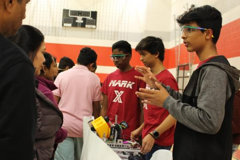 Mark X Robotics club leaders junior Aryan Damle and two other Coppell ISD students tell parents more about their club in the CHS9 small gym at the Spring Showcase. The annual event took place from on Jan. 27 and allowed incoming freshmen and their parents to tour the campus and learn about course and extracurricular opportunities.