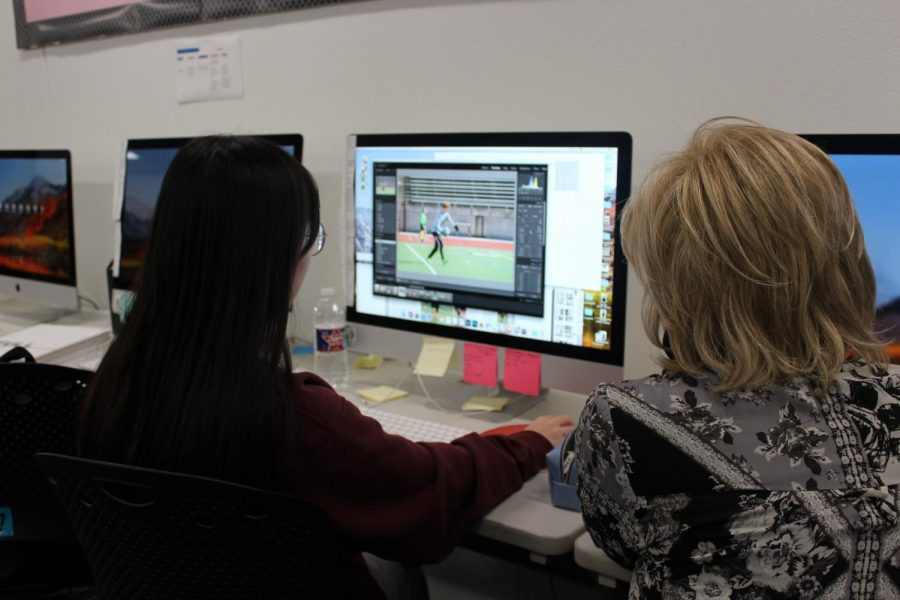 Coppell High School junior photo editor Sujeong Oh walks Round-Up yearbook adviser Sallyanne Harris through edits of soccer photos on Thursday. March 6 is the final day to send off pages of this year's yearbook to be published.