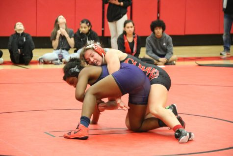 New Tech High @ Coppell senior captain Brooke Massaviol wrestles in top position against Frisco Independence junior Sariah Ferguson at the Knockout Sportswear Cowgirl Classic on Dec. 6 in the CHS Arena. Massaviol is currently the No. 1 ranked girls wrestler in the 148 pound weight class in the state.