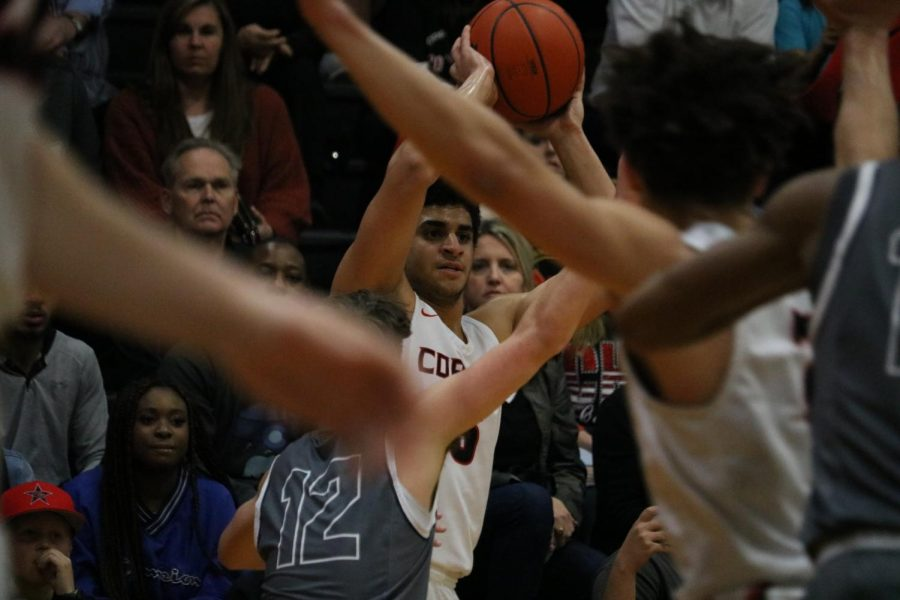Coppell senior guard Adam Moussa looks for a teammate agaistEaton last night at Trinity High School in Euless. The Cowboys defeated Eaton, 80-46, in Class 6A Region I bi-district playoffs.