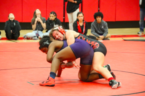 New Tech High @ Coppell senior captain Brooke Massaviol wrestles in top position against Frisco Independence junior Sariah Ferguson at the Knockout Sportswear Cowgirl Classic on Dec. 6 in the CHS Arena. Massaviol has qualified for today and tomorrow's UIL State Wrestling Championship after placing third in the 148 pound weight class in the Class 6A Region II Championship match.