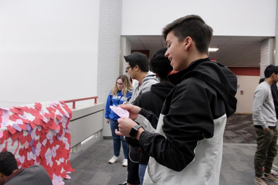 Coppell High School senior Santi Ceniceros reads his heart on the senior bridge during sixth period today. Student Council wrote compliments for every student at CHS and hung them up in the halls for Valentine's Day.