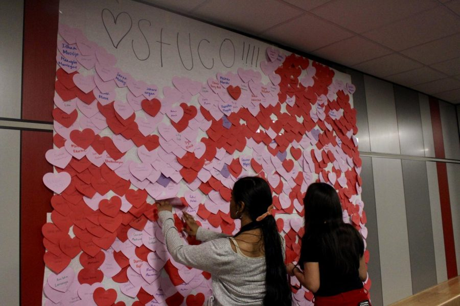 Coppell+High+School+juniors+Deepika+Tadepalli+and+Brianna+Perez+look+for+their+hearts+on+the+11th+grade+wall+in+C+hall+during+sixth+period+today.+Student+Council+wrote+compliments+for+every+student+at+CHS+and+hung+them+up+in+the+halls+for+Valentine%E2%80%99s+Day.