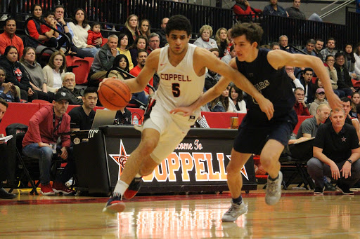 Coppell senior guard Adam Moussa dribbles around Flower Mound senior Preston Evans yesterday at the CHS Arena. The Cowboys defeated the Jaguars, 66-56.