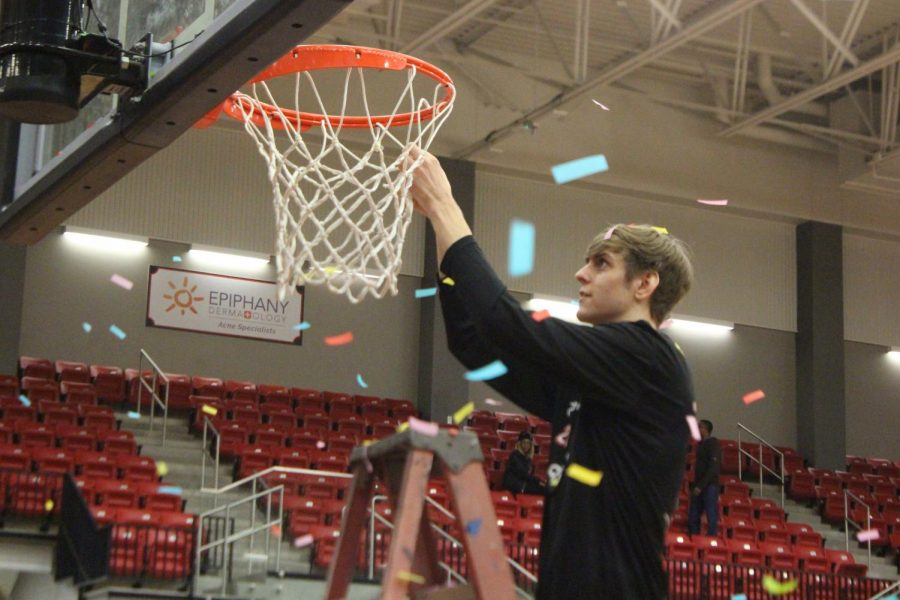 Coppell senior forward Clayton Hunter cuts a piece of net after defeating Hebron, 85-53, last night in the CHS Arena. The basketball team celebrated its District 6-6A championship by keeping these pieces as souvenirs.