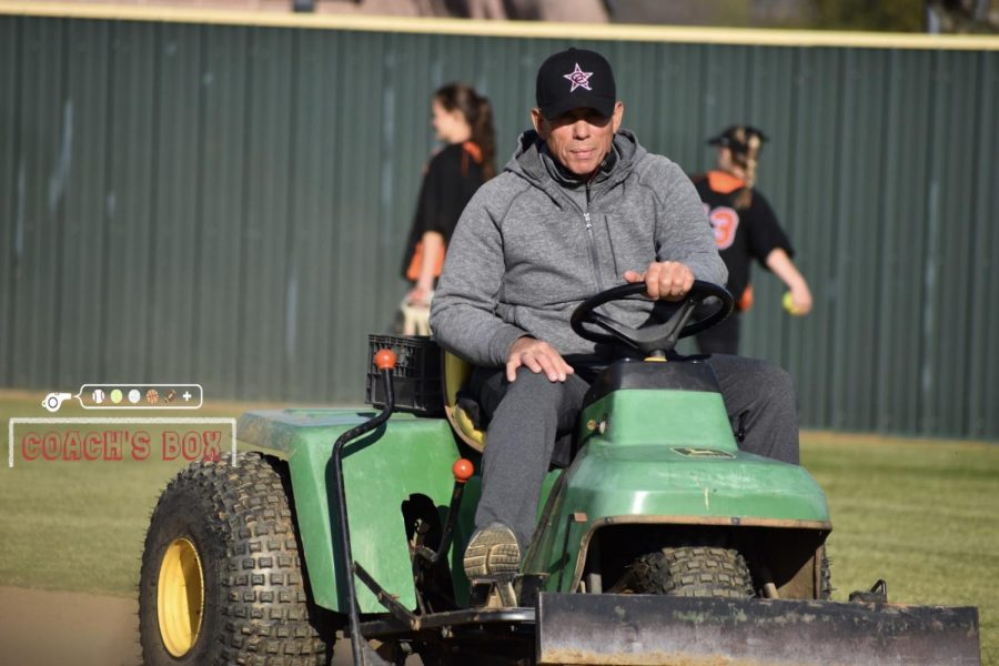 Coppell coach Mike Dyson rakes the infield at the Coppell ISD Softball Complex on March 7, following the Cowgirls' victory over Cedar Hill, 7-5, at the Coppell & Marcus Tournament. Dyson is in his fifth year of coaching the Coppell softball team.