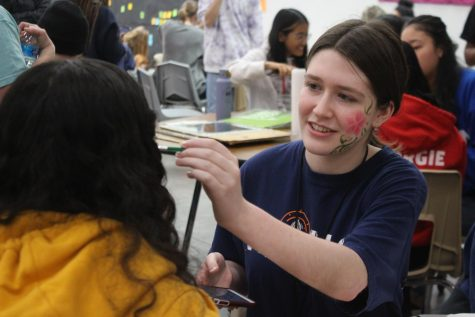 Coppell High School junior Jordan Cohen paints a flower on sophomore Arshi Sharma during A lunch in the Large Commons on Thursday. Students in National Art Honor Society throughout the day orchestrate art activities during all lunches today.