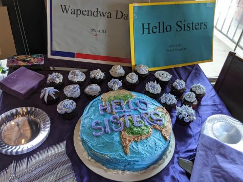 Homemade cakes and cupcakes are arranged on a table alongside signs that read 'hello sisters' in different languages at a Women's Day event at Andalous Mediterrean Buffet in Richardson on March 8. The event commemorated International Women's Day and Women's History Month.