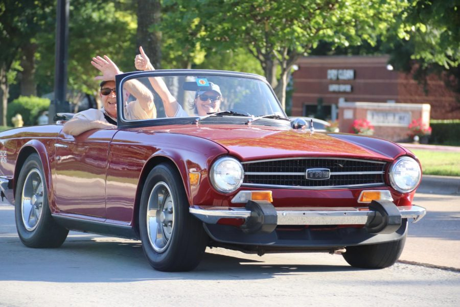 Coppell residents drive a Triumph TR6 in a pop-up parade down Denton Tap Road on April 23. In efforts to keep the local economy strong and maintain social distancing rules, residents were encouraged to order take-out from their favorite Coppell restaurant and have a picnic in their car as they watched the parade go by.