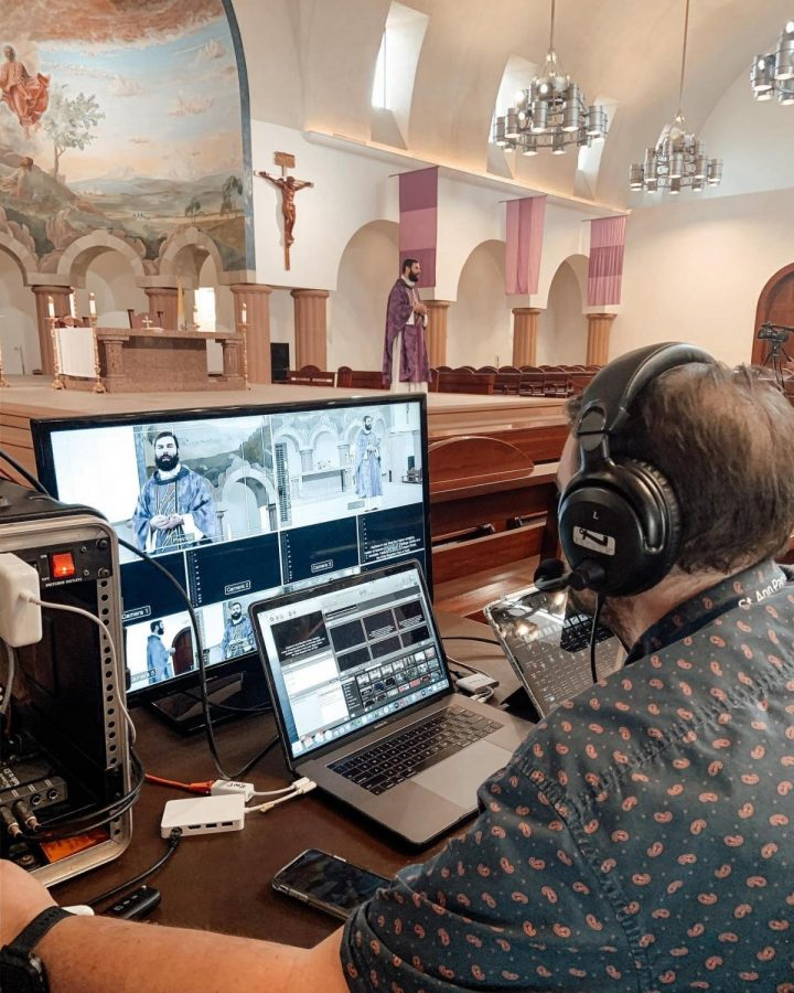 St. Ann Catholic Parish director of youth ministries Joey Seaneella operates recording technology as Fr. Paul Bechter gives a sermon. St. Ann is one of the many local religious institutions that has turned to live streaming to provide its services. Photo courtesy Kurt Klement