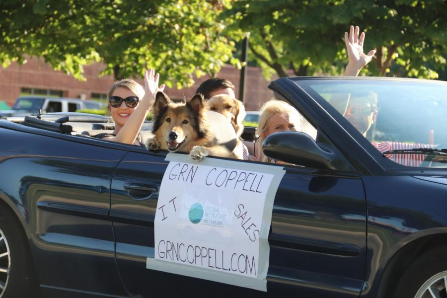 Members of the Global Recruiters of Coppell promote their business by participating in a pop-up parade down Denton Tap Road on Thursday. In efforts to keep the local economy strong and maintain social distancing rules, residents were encouraged to order take-out from their favorite Coppell restaurant and have a picnic in their car as they watched the parade go by.