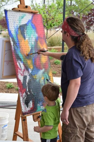 Coppell High School Art I, Honors Art I and Sculpture II teacher David Bearden paints with his son, Oliver, during the Colorpalooza arts festival in Lewisville in April 2019. Bearden's teaching experience and love for creating art impact his students and his classroom environment.