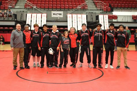 Coppell wrestling coach Chip Lowery (far left) takes a photo with senior wrestlers on Senior Night at the CHS Arena on Jan. 31. Lowery is also the physical education and dance department chair and off campus P.E. director.