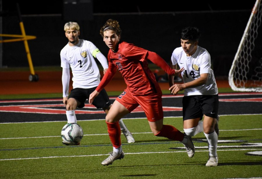 Coppell+senior+forward+Sebastian+Blaas+avoids+the+grasp+of+Irving+MacArthur+to+make+a+pass+on+Feb.+7.+Blaas+is+one+of+13+Cowboys+to+be+selected+for+a+District+6-6A+award.+
