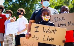 Young protestor, Ben, holds up his sign in order to support the Black Lives Matter movement at Town Center Plaza in Coppell on Wednesday. The Coppell community rallied together to spread awareness about BLM and fighting against racial injustice.