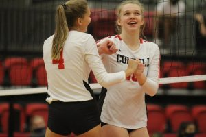 Coppell junior right-side hitter Abigail Hendricks and sophomore outside hitter Reagan Engler celebrate in the CHS Arena on Friday. Coppell defeated Prosper Rock Hill, 25-23, 25-18, 25-11.