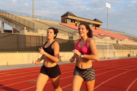 Coppell senior Chloe Hassman and junior Waverly Hassman run during cross country practice at Buddy Echols Field on Tuesday morning. Hassman committed to the University of Pennsylvania for track and field and cross country on Aug. 22. Photo by Lilly Gorman.