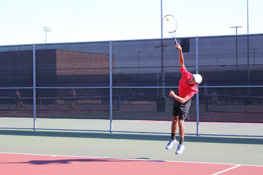 Coppell junior Atharva Nijasure makes an overhead shot during the team's match against Marcus at the CHS Tennis Center yesterday. Coppell won the match, 15-4.