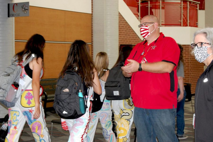 Coppell High School assistant principal Zane Porter greets students before school on Aug. 28 in the main hallway. Porter became one of the assistant principals for CHS in May after teaching at New Tech High @ Coppell for four years. Photo by Nandini Muresh