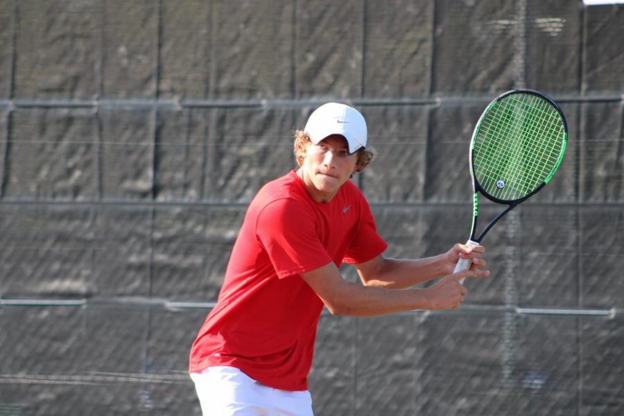 Coppell junior Cason Cole backhands during his doubles match at the CHS Tennis Center on Friday. The Coppell tennis team hosts Marcus today at 4 p.m. at the CHS Tennis Center.