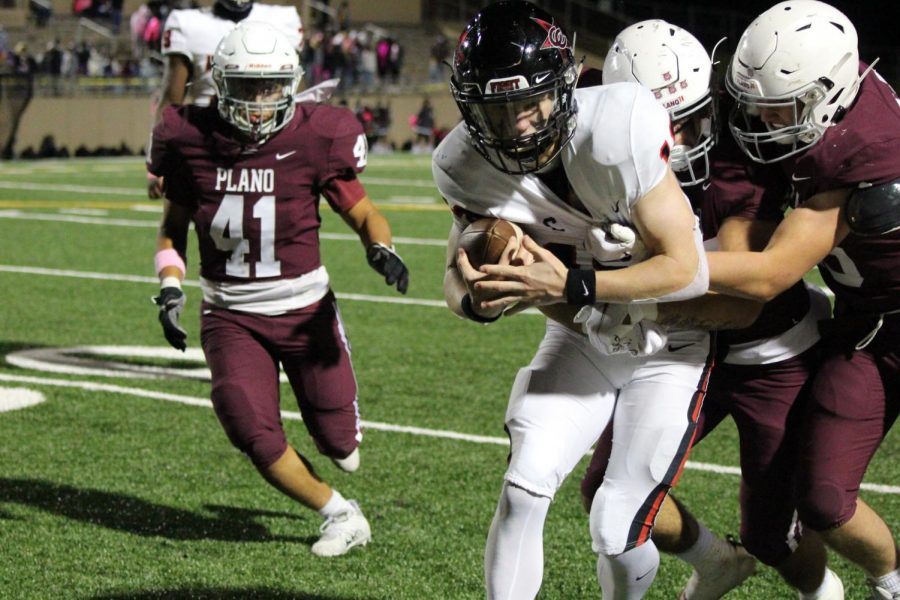 Coppell senior quarterback Ryan Walker is tackled by Plano defenders at John Clark Field last night. Coppell defeated Plano, 35-33.