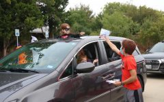 Coppell families drive through the Halloween Candy Cruise on Saturday at the Coppell Senior & Community Center. Distributors wearing masks pass out candy to residents in cars as a safer alternative to traditional trick-or-treating.