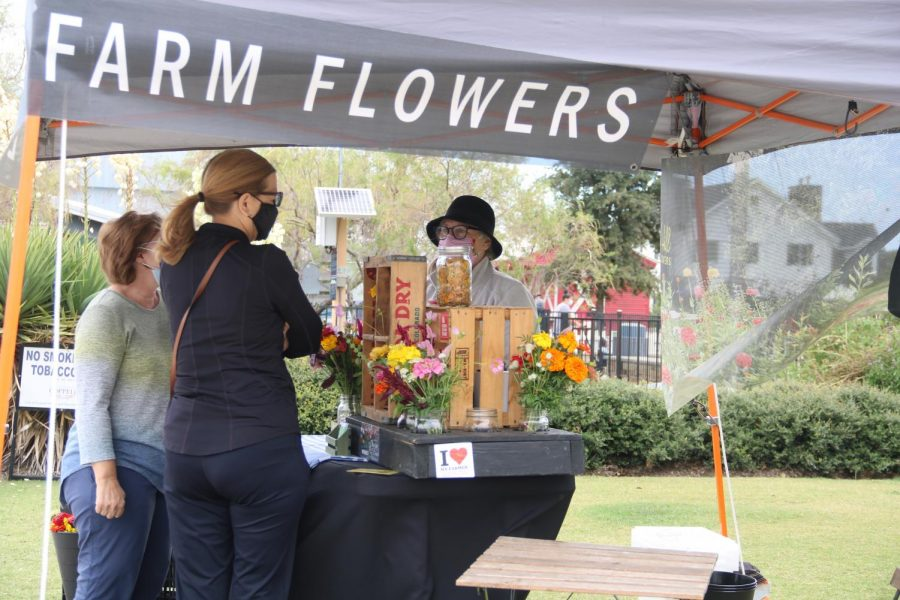 Coppell residents visit the Farmers Market on Saturday in Old Town Coppell. Due to COVID-19 restrictions, people distance from others and wear masks while stopping by spaced out vendors. Photo by Nandini Muresh