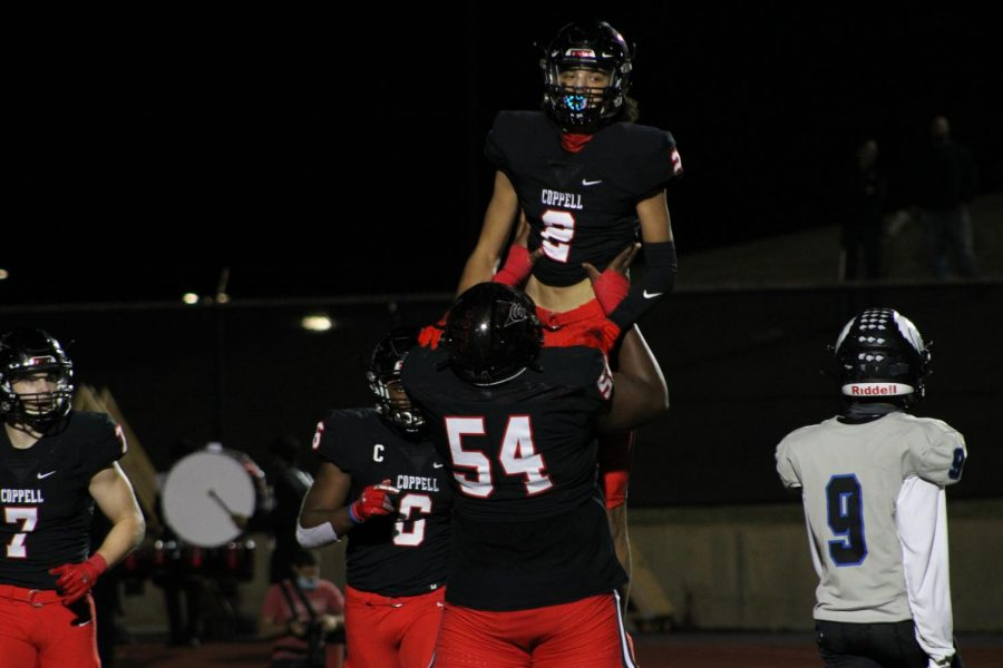 Coppell senior offensive lineman Febechi Nwaiwu and junior wide receiver Anthony Black celebrate Black's touchdown in the second quarter against Plano West last night at Buddy Echols Field. Coppell defeated Plano West, 31-20, in its annual Homecoming game.