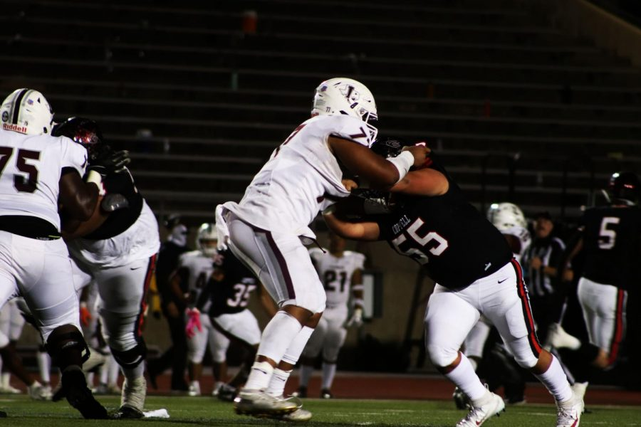 Coppell junior defensive lineman Sammy Hernandez grapples with Lewisville junior offensive lineman Tahj Martin during the third quarter last night at Buddy Echols Field. The Cowboys fell to the Farmers, 39-14, in a disheartening Senior Night loss.