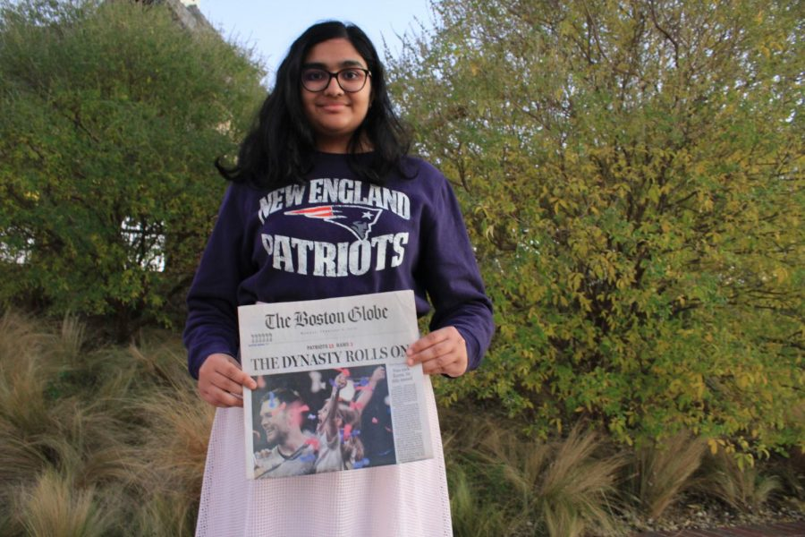 The+Sidekick+junior+staff+writer+Anjali+Vishwanath+shows+her+team+loyalties+with+a+sweatshirt+and+newspaper+article+describing+the+New+England+Patriots%E2%80%99+2019+Super+Bowl+win+at+Andy+Brown+East.+Vishwanath+moved+from+Massachusetts+to+Texas+in+2018%2C+but+finds+that+her+loyalty+remains+with+New+England+sports+teams.