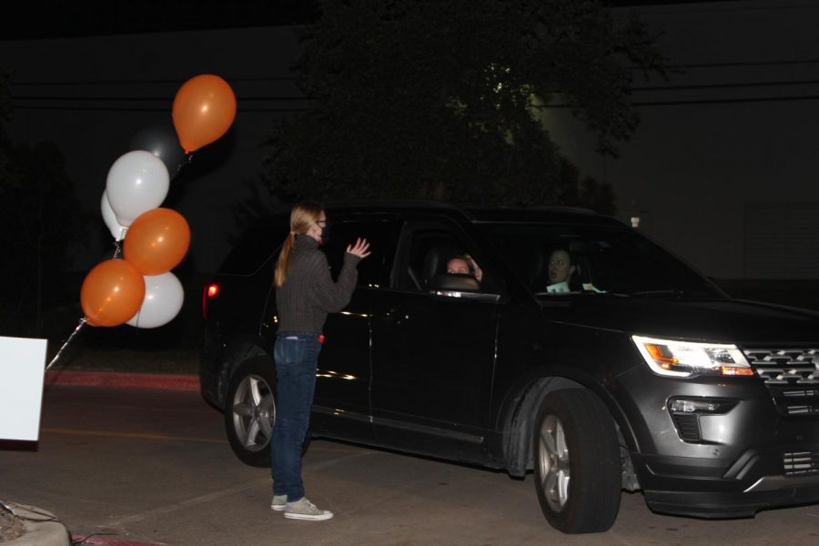 Coppell High School senior Lauren Myers guides cars into the CHS9 parking lot before the CHS theater-produced movie begins on Thursday. The Cowboy Theatre Company's Terrifying Texas Tales drive-in movie was a safe way to have a performance during COVID-19.
