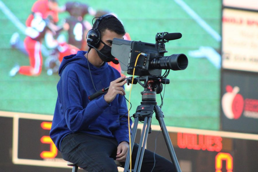 Coppell High School senior Parth Mahajan adjusts his camera for the KCBY-TV livestream of the homecoming football game against Plano West on Friday at Buddy Echols Field. This year, KCBY is livestreaming every home football game and volleyball match for people to watch from their homes.