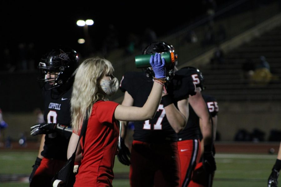 Coppell High School senior London Hurt brings water to the Coppell football team during a timeout at Buddy Echols Field against Plano West on Oct. 30. The athletic trainers have experienced many changes due to COVID-19, such as wearing masks to follow the Centers of Disease Control Prevention guidelines to keep the staff and students safe.