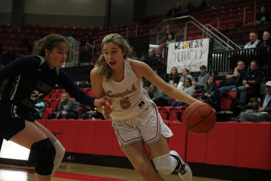 Coppell sophomore guard Jules LaMendola dribbles past Flower Mound last season at the CHS Arena on Feb. 20. The Cowgirls are under quarantine until Nov. 19 after identifying a positive COVID-19 test result. Sidekick File Photo.