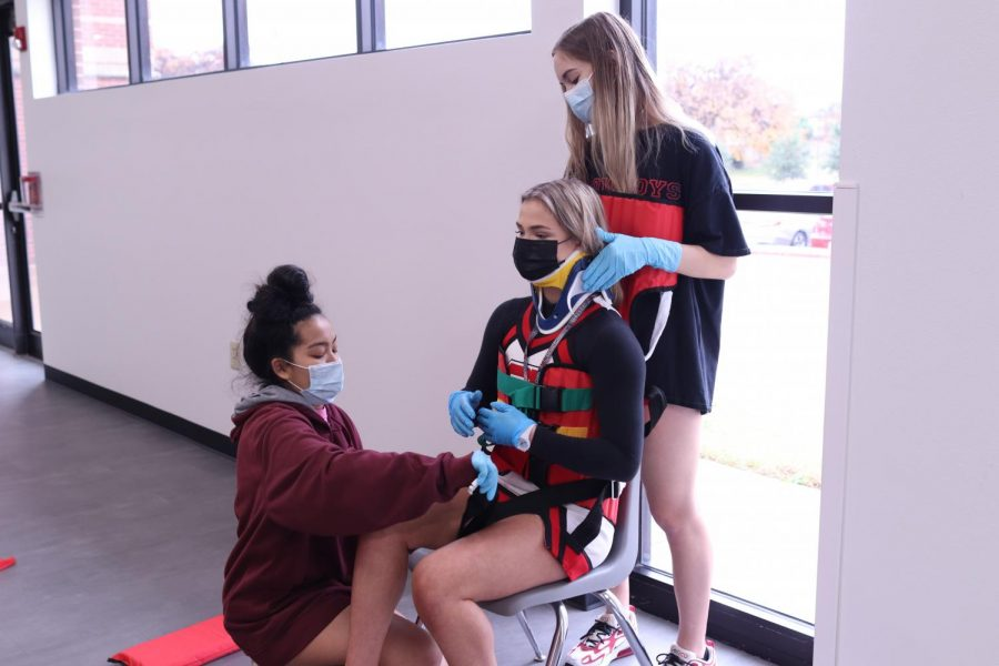 Coppell High School seniors Jaden Escoto and Kimberly Henze practice strapping CHS senior Emersyn Jorski in medical equipment during CHS EMT and pharmacy tech teacher Gary Beyer's seventh period class on Friday. CTE courses are expanding their offerings at CHS and rebranding themselves.
