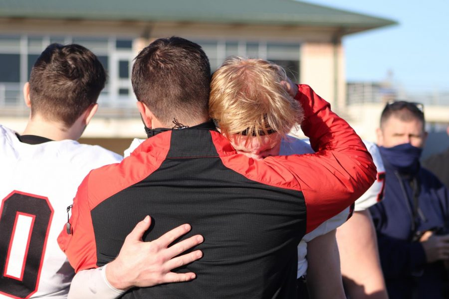 Coppell senior quarterback Ryan Walker hugs Coppell assistant Lincoln Hanke following Denton Guyers 52-24 victory at C.H. Collins Athletic Complex on Saturday in the Class 6A Division II Region I bi-district playoffs. Coppell ends its season 6-4.
