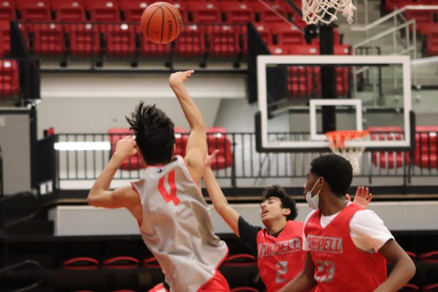 Coppell sophomore guard Caleb Soto shoots against junior guard Devank Rane and senior small forward Obi Odimegwu during first period practice on Dec. 3. The Coppell boys basketball team is in quarantine until Friday due to COVID-19.