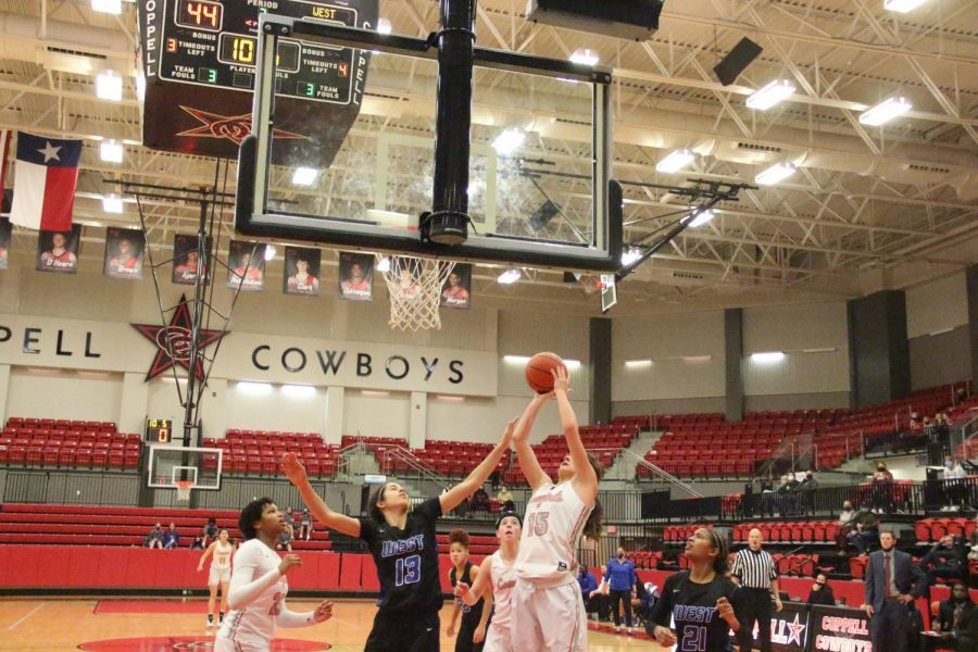 Coppell junior shooting guard Chloe Hassman shoots a jump shot against Plano West sophomore small forward Sibelle Zambie at the CHS Arena on Tuesday. Coppell defeated Plano West, 66-65, in overtime.