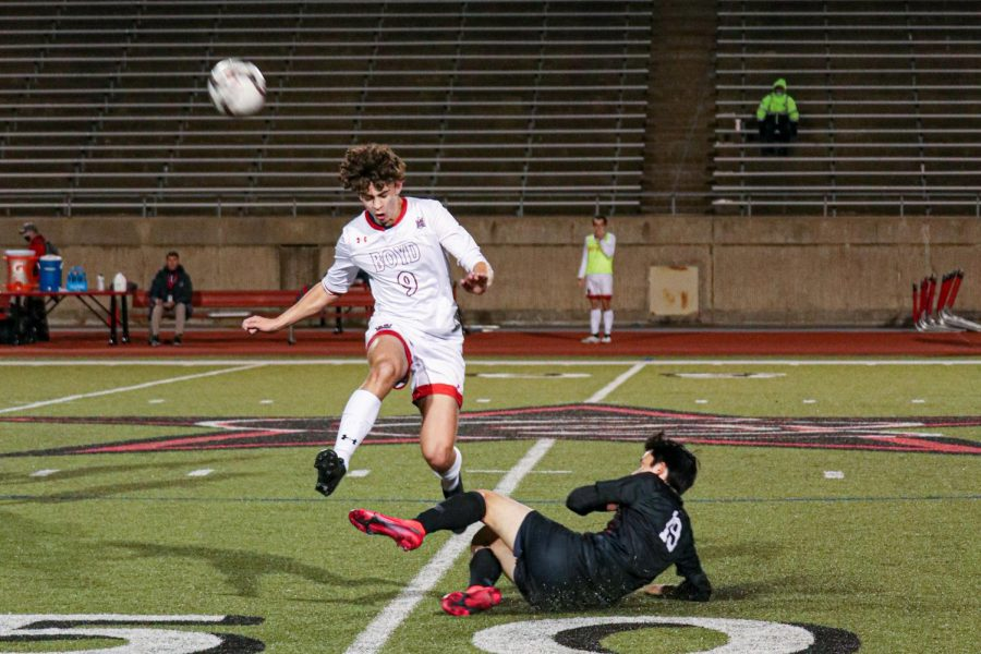 Coppell senior defender Victor Salvo slides under McKinney Boyd senior forward Mackay D Fisher and steals on Jan. 19 at Buddy Echols Field. The Cowboys defeated the Broncos, 2-1.