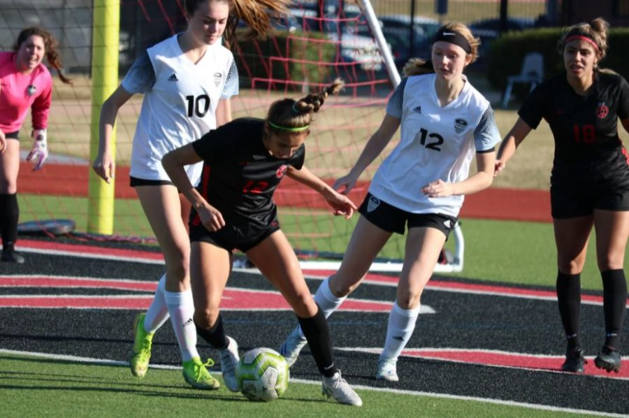 Coppell senior forward Jojo Alonzo dribbles against Hebron junior defender Hannah Elliott and Parker Coe on Feb. 6 at Buddy Echols Field as Coppell junior forward Reneta Vargas looks on. The Cowgirls host Marcus at 7:30 p.m. tomorrow.
